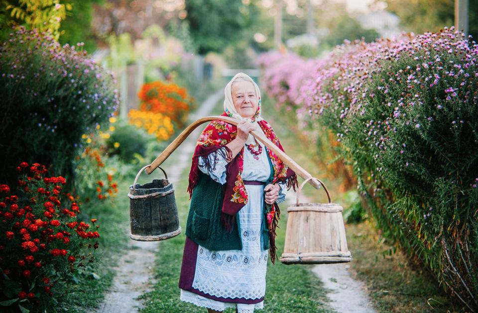 Пожилая женщина в традиционном костюме несет воду из колодца. «Хутор Савки» в Новых Петровцах, Украина