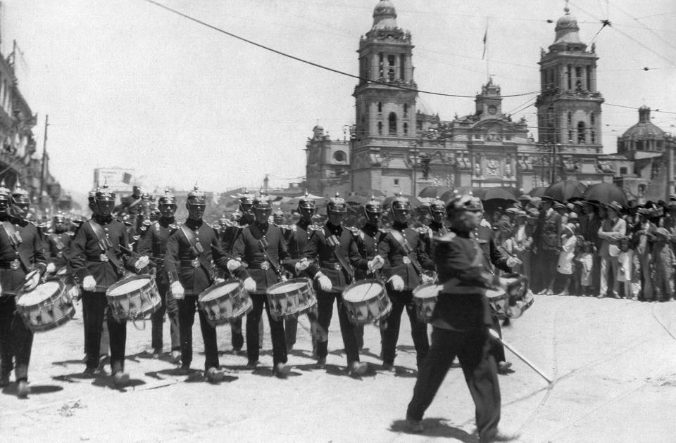 Фотограф запечатлел военный парад на площади Конституции в Мехико в честь столетия независимости Мексики, которое отмечалось в 1910 году. Торжества пришлись на время правления Порфирио Диаса. Этот период запомнился подъемом экономики: строились железные дороги и телеграфные линии, создавались новые предприятия, увеличился приток иностранных инвестиций. Правда, во многом эти результаты были получены за счет эксплуатации крестьян